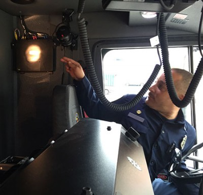 Fire Apparatus Engineer Gerad Bullard points at AVL Unit in Cal Fire Water Tender