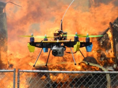 Drone hovering in front of burning house