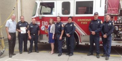 Ramona firefighter, who received a 2019 grant, stand by their firetruck